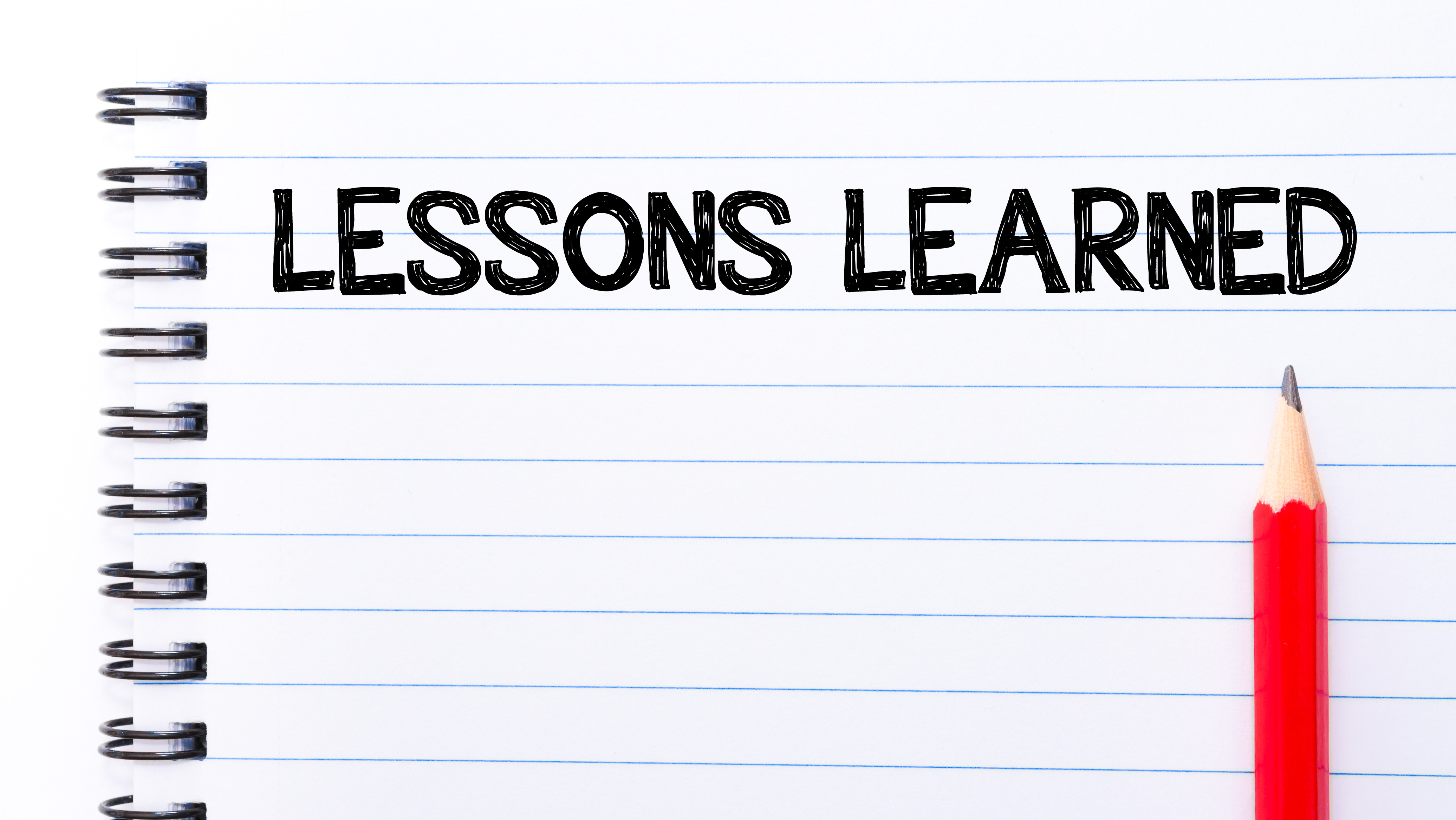 Lessons Learned Text written on notebook page, red pencil on the right. Motivational Concept image